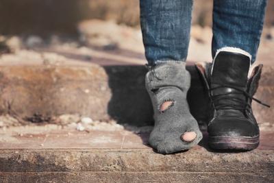 Poor woman wearing old socks